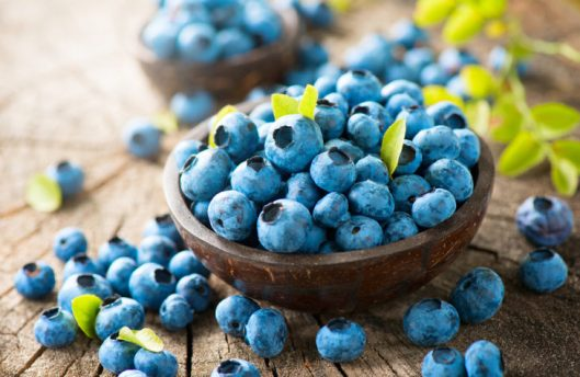 Blueberry on wooden table background. Ripe and juicy fresh picke